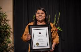 Valerie Olivares holds a framed award.