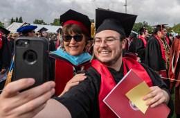 President Hutchinson and Joseph Arballo pose for a selfie at graduation, both in their regalia.