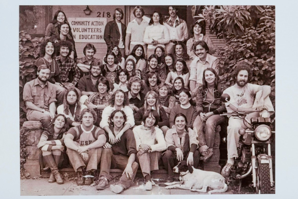 A historic photo of CAVE shows its staff sitting on the building stairs in the early 1970s.