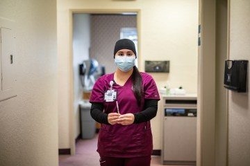 A nursing student wearing protective gear holds a syringe that contains the vaccine against the coronavirus.