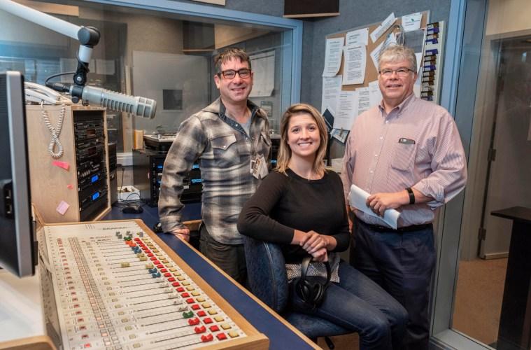 Three NSPR employees sit in a news studio among radio equipment.