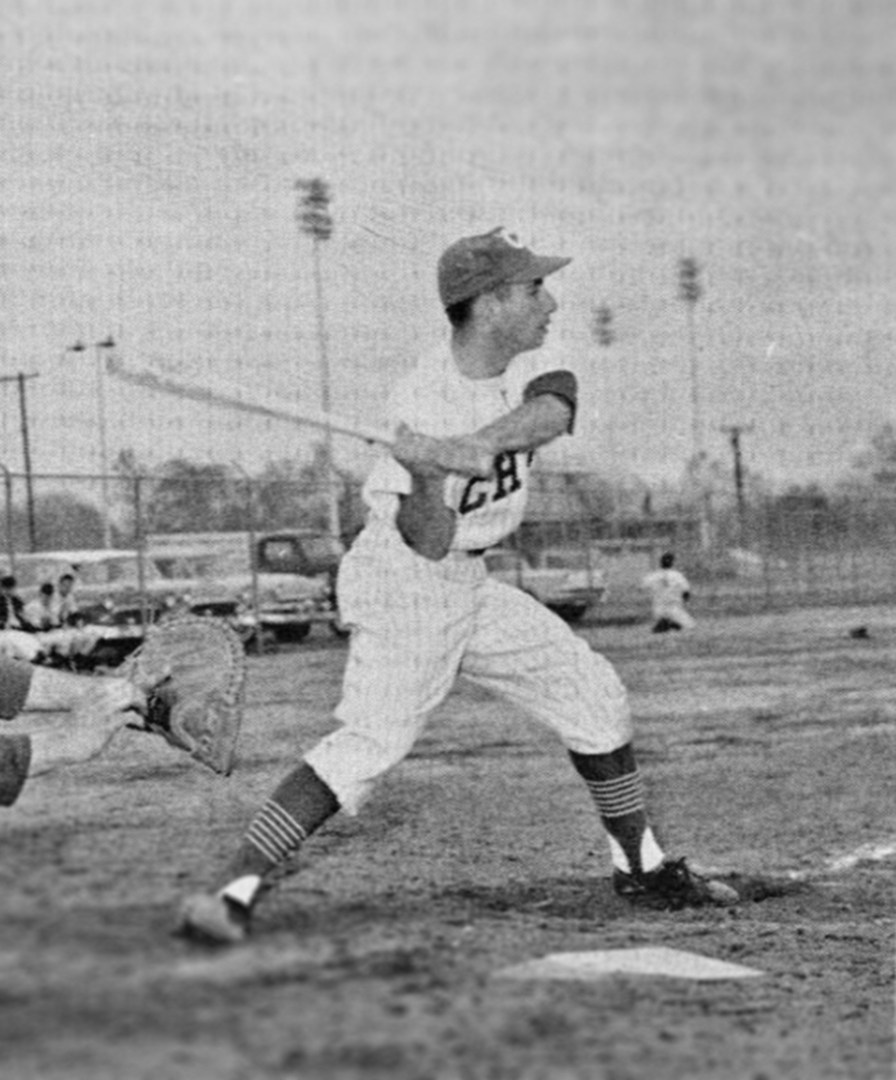 A black and white photo shows a Chico State player swinging at a pitch at home plate decades ago.