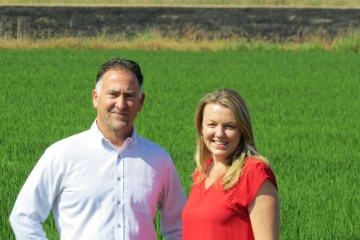 Erin O'Donnell and Steve Vargas stand in a rice field.