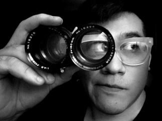 Octavio Valencia looks through a photo lens.