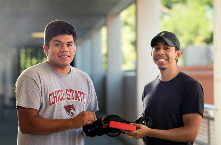 Two students smile and together hold a knee brace prototype.