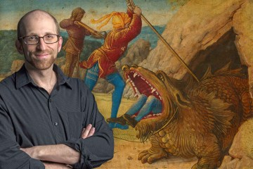 Asa Mittman stands in front of a painting of a monster with a person's feet sticking out of its mouth as humans attempt to stab it.