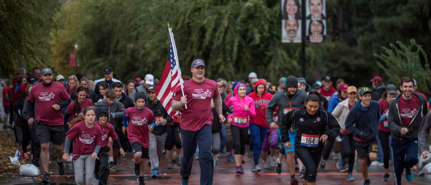 Mike Guzzi runs with the American flag in front of dozens of people, leading them across campus in a 5K run/walk