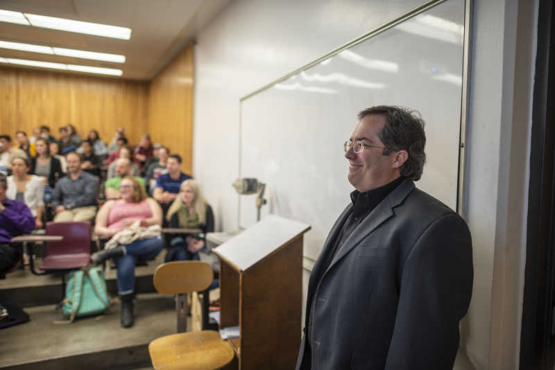 Sam Clegg smiles as he prepares to talk to a group of Chico State students inside a classroom.