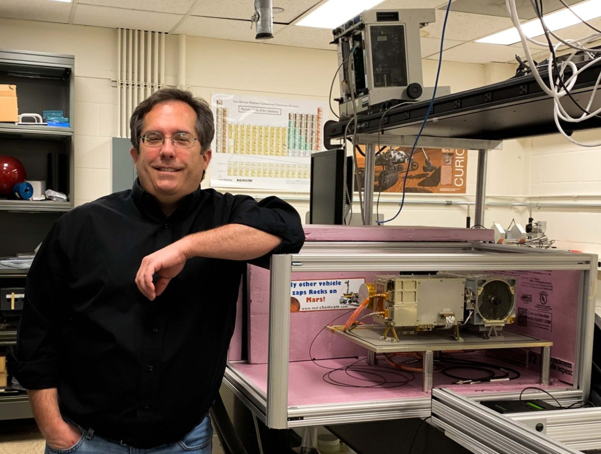 Sam Clegg poses with the research equipment he works on, which is enclosed in a clear case.