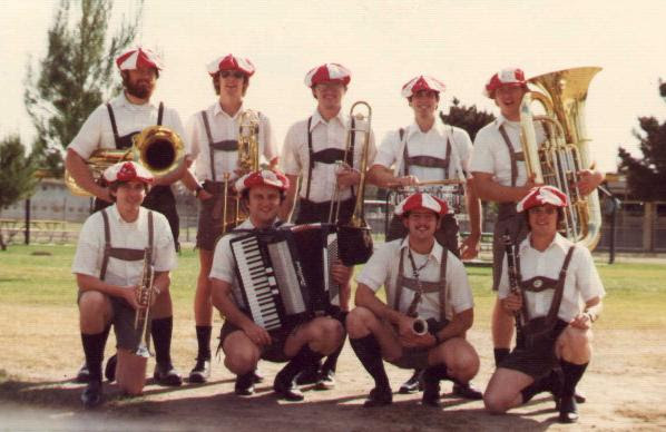 Nine men stand holding their various musical instruments outside while wearing lederhosen and red and white hats.