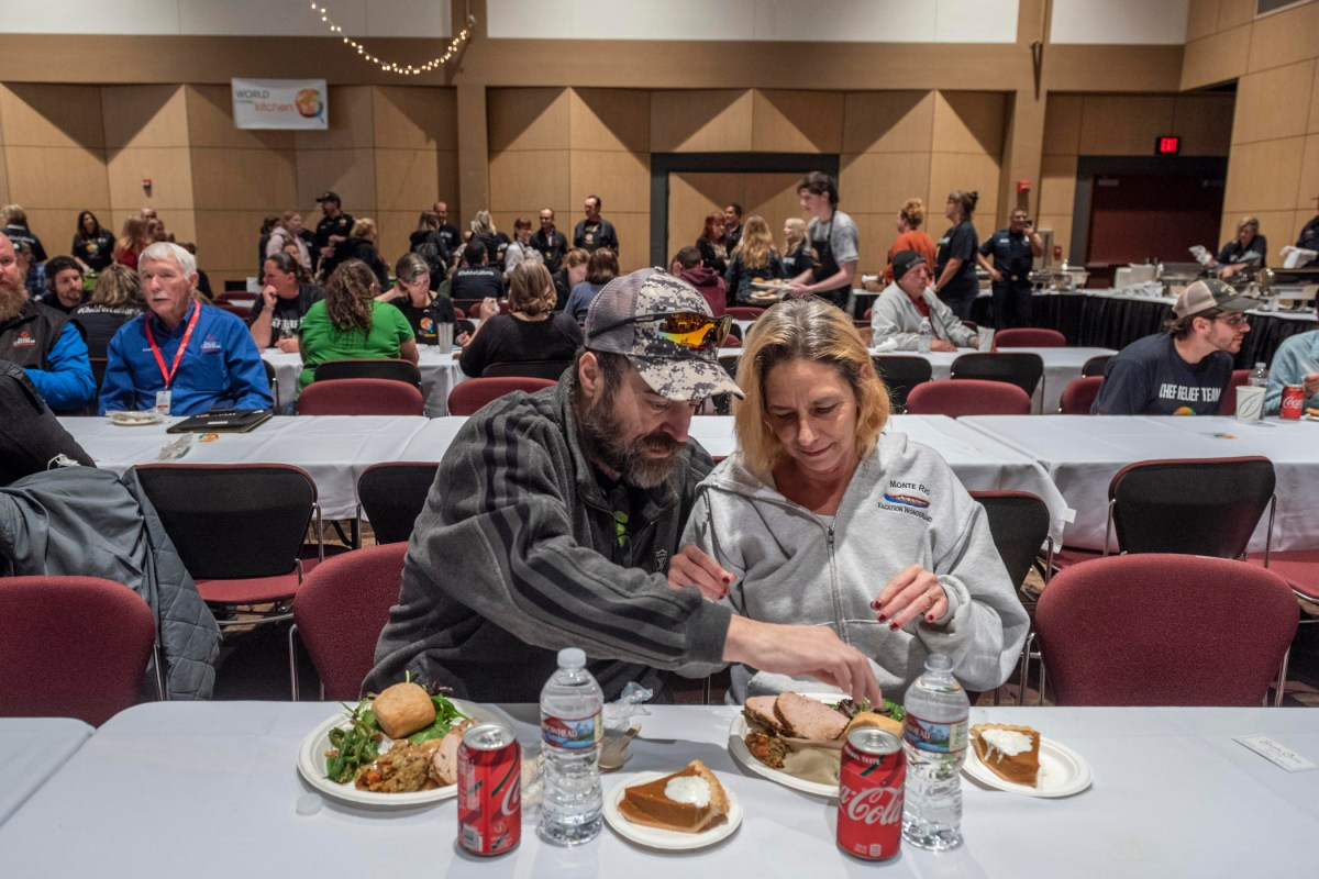Two people eat a Thanksgiving meal at a row of tables in the Bell Memorial Union Auditorium.