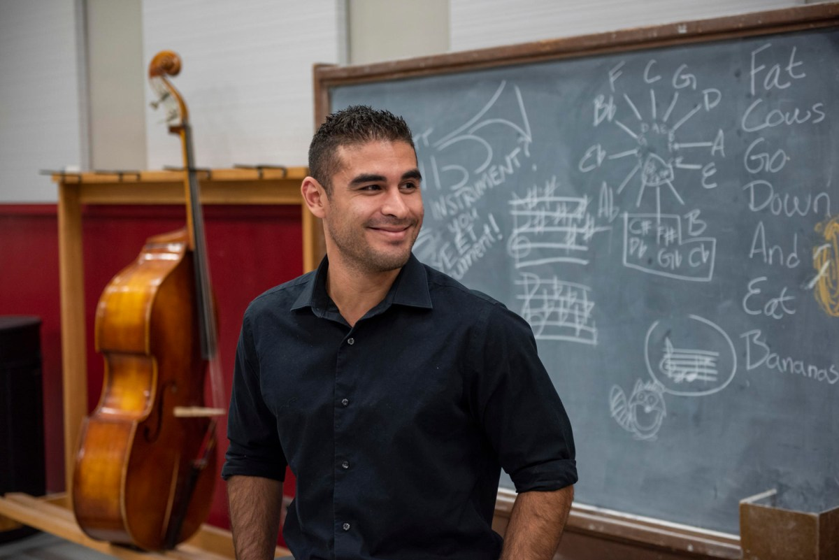 Chris Navarrete smiles and stands in front of a blackboard and a cello