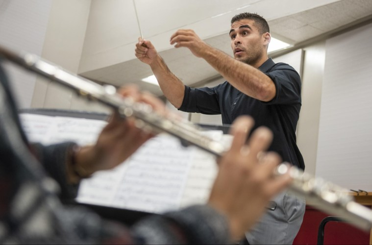 Chris Navarrete conducts a music rehearsal with a clarinet player playing in the foreground