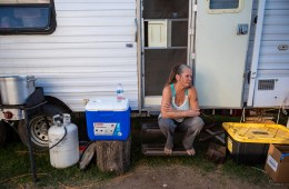 A woman sits on the outdoor step of her travel trailer.