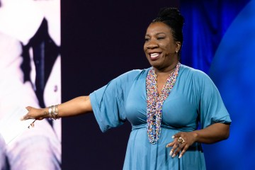 Tarana Burke gestures with one arm while speaking on a stage.