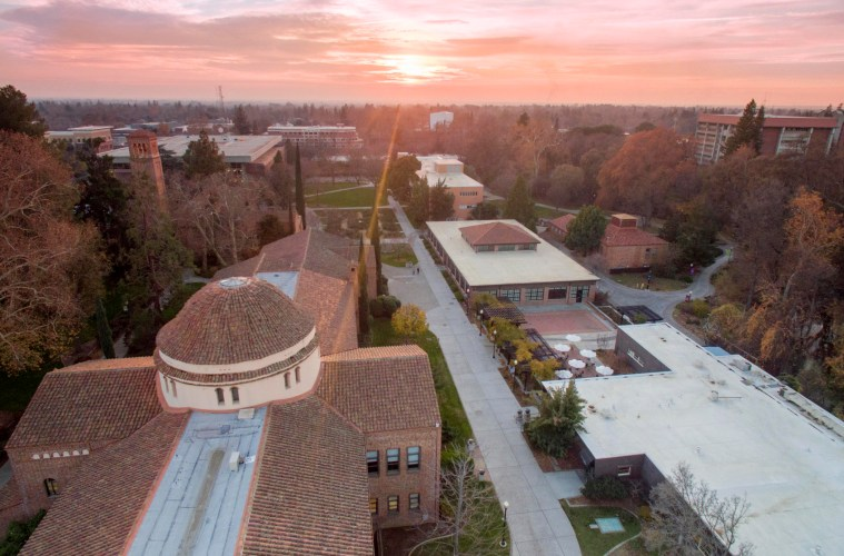 A drone photo of a sprawling college campus with the sun setting in the background.