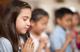 A young girl clasps her hands in prayer with her eyes closed.