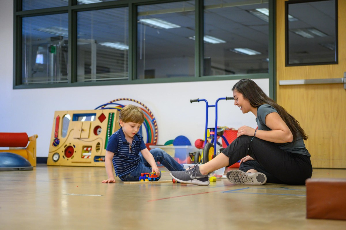 A student and young boy work with small toys on the floor of the autism clinic.