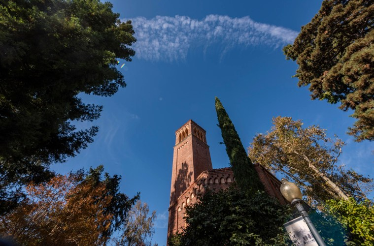 Puffy white clouds drift past trees and Trinity Tower.