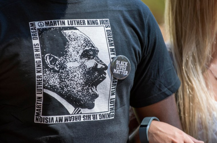 A person wearing a Martin Luther King Jr t-shirt and a Black Lives Matter pin locks arms with another person.