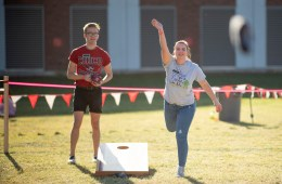 Students throw bean bags as part of a cornhole tournament.