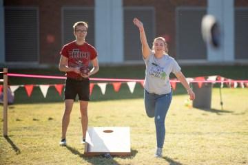 Students throw bean bags as part of a cornhole tournament.