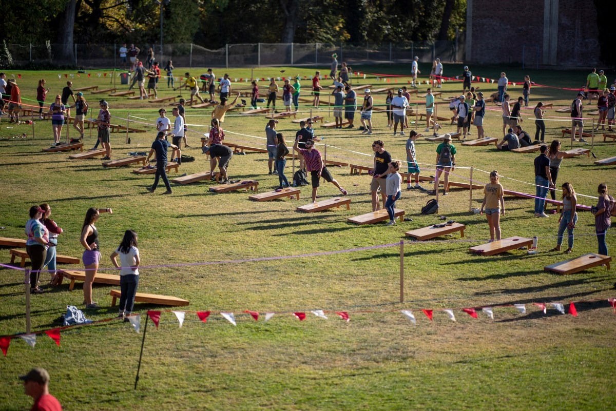 A distanced view show dozens of teams playing corn hole on the Yolo Hall field.