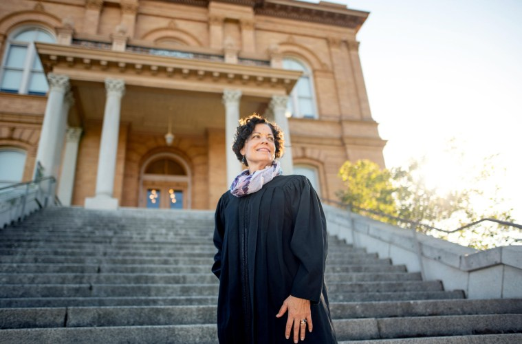 Portrait of Colleen Nichols standing on the steps of a courthouse