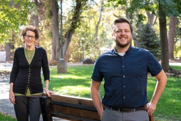 Jacque Chase places her hand on a sitting bench and Peter Hansen smiles as they stand among grass and trees.