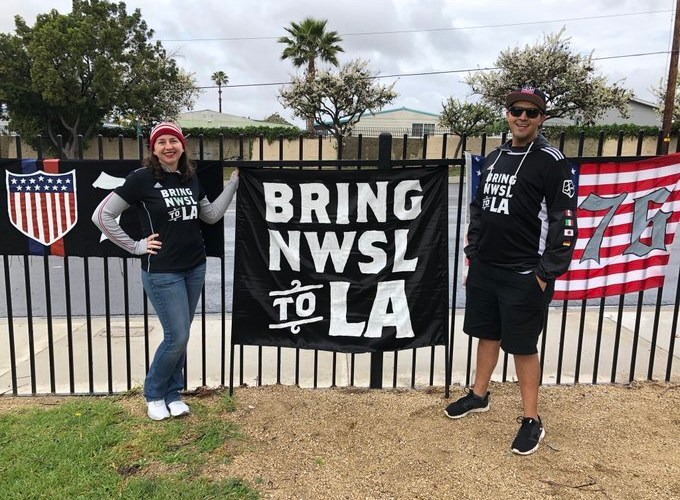 "Mark and Lindsay Rojas stand with a ""Bring NWSL to LA"" flag"
