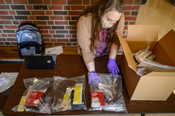 Lisa Kendhammer fills plastic bags with chemistry equipment for at-home experiments.