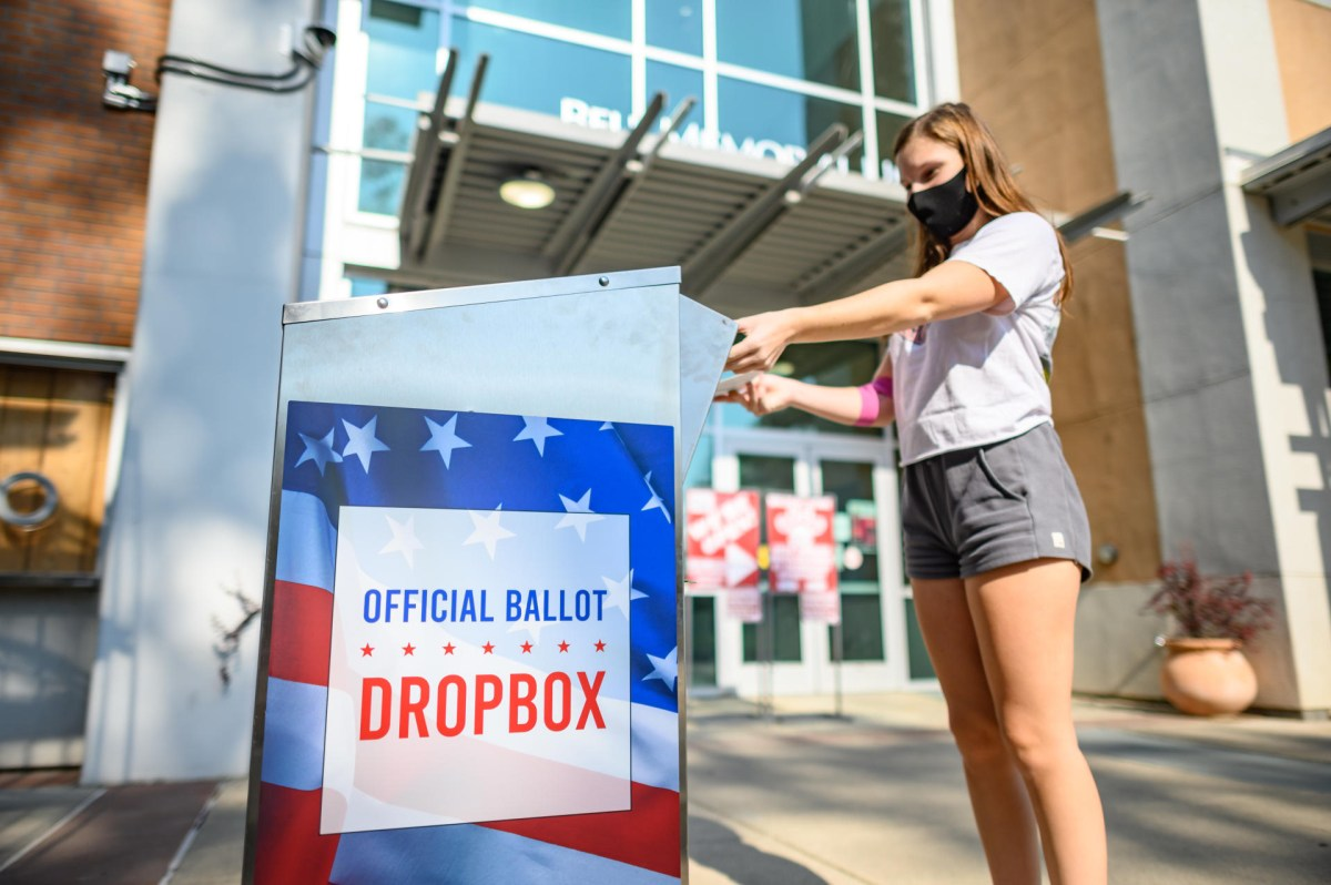 A student drops a ballot in an official drop box in front of the Bell Memorial Union.