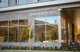 The exterior of the science building includes large windows and native plant landscaping.