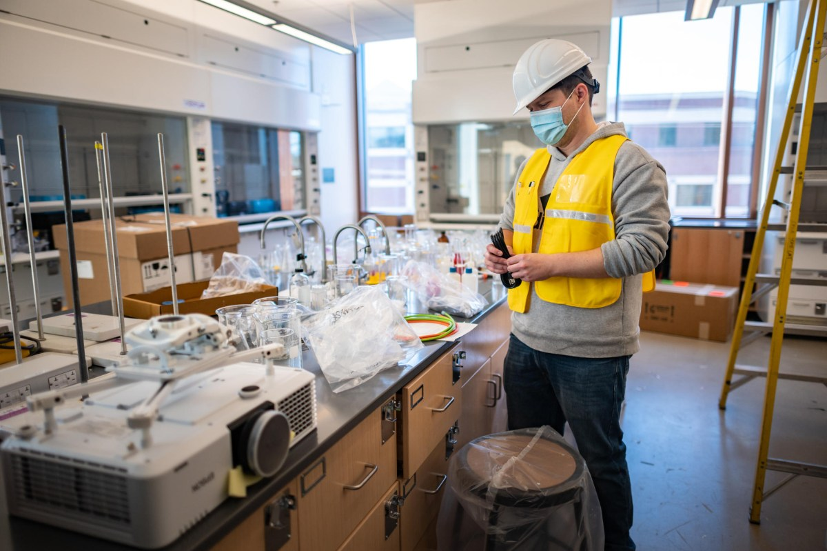 A person in a hard hat unwraps lab technology such as beakers and other tools in a new laboratory classroom.