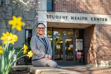 Juanita Mottley sits on a concrete bench with flowers to her right and in front of the Student Health Center