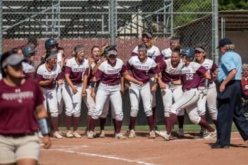 A team of college softball players line up and cheer for a teammate as she prepares to touch home plate.