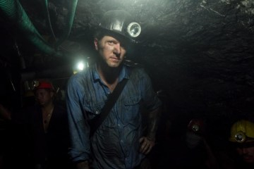 Brian Brazeal wears a helmet with a headlamp in a dark mine shaft.