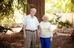 Tom and Melaine Taylor hold hands in front of a redwood tree on campus.