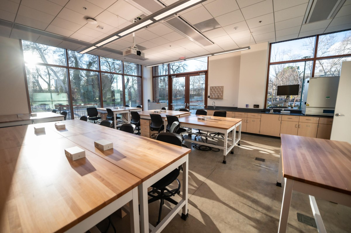 Groups of desks are illuminated by light streaming in wide floor to ceiling windows in a classroom in the new Science Building.