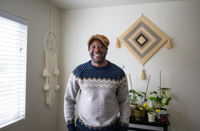 Kris Walker poses and smiles in his home with a shelf full of plants behind him