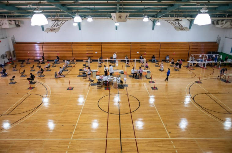 Students and healthcare workers sit in chairs inside a basketball gym.