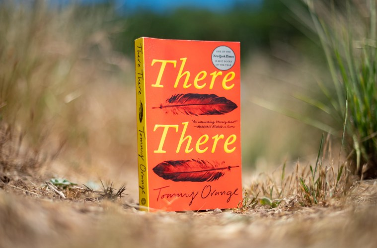 """A book titled """"There There"""" sits among a field of grass."""