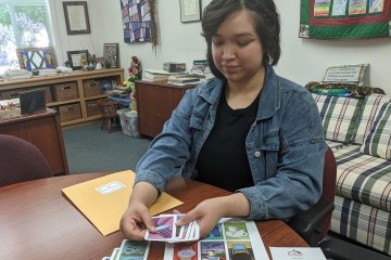 Karen Victorio sits at a desk and distributes COVID-10 themed loteria cards