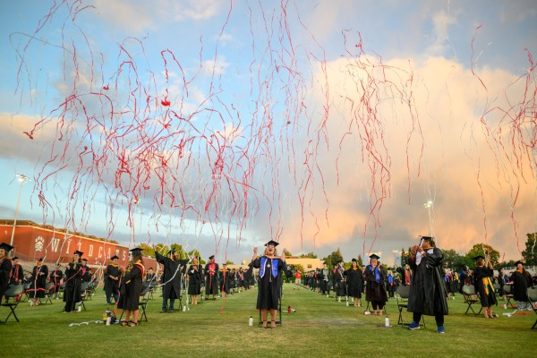 Streamers fall to the ground as masters graduates celebrate their Commencement.