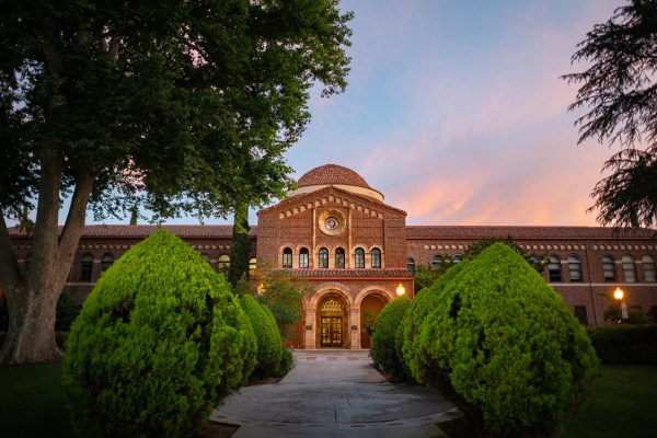 An academic building sits in the early evening sun with colorful clouds swirling behind.