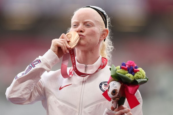 Kym Crosby kisses her bronze medal during the medal ceremony for the 400M at the Tokyo 2020 Paralympics