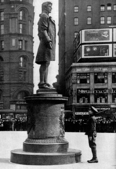 A World War I soldier stands beside a Nathan Hale statue in New York City.