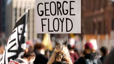 A protester holds a George Floyd sign outside the Hennepin County Courthouse in downtown Minneapolis