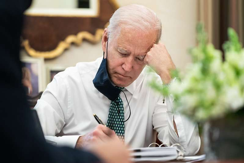 President Joe Biden takes notes during a briefing on the shootings in Atlanta Wednesday