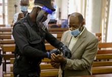 A policeman handcuffs Paul Rusesabagina